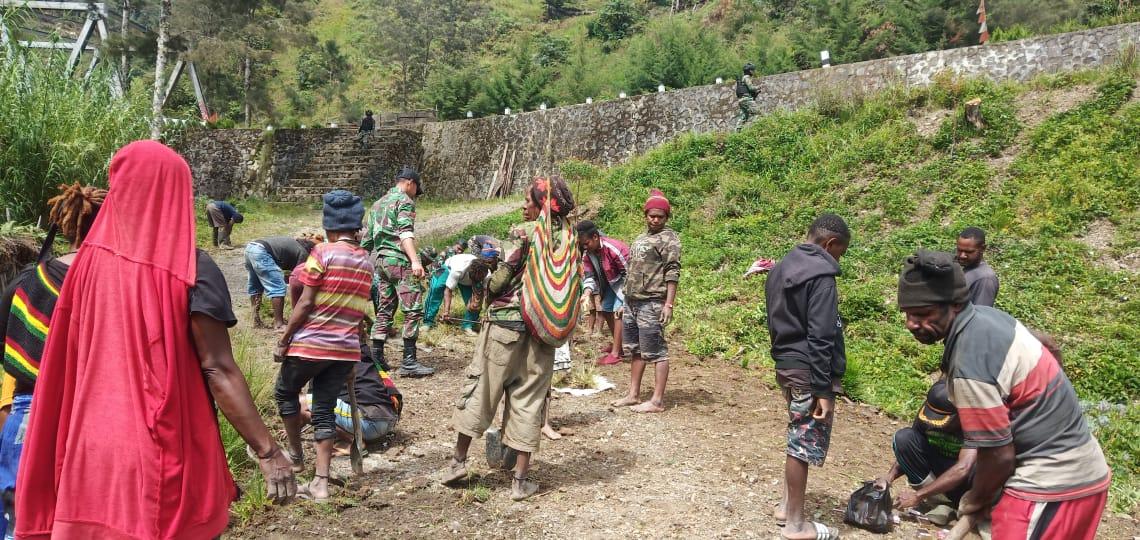 Bersama masyarakat, Satgas Yonif RK 751/VJSbersihkan jalan dan kantor desa di Distrik Kubu